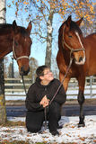 Tonåringpojke och två bruna hästar Royaltyfri Foto