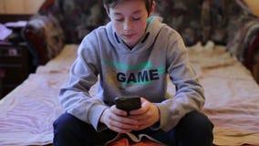 Tonåringpojke som spelar i lek på Smartphone stock video