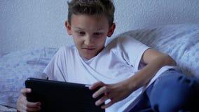 Tonåringpojke som talar av videoen som antecknar berättelser på minnestavlan