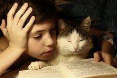 Tonåringpojkeläsebok i säng med att sova katten Royaltyfria Bilder