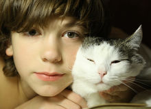 Tonåringpojkeläsebok med katten i säng Royaltyfria Foton