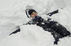 Tonåringpojken ligger i djup snö under ett tungt snöfall arkivbild