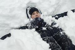 Tonåringpojken ligger i djup snö under ett tungt snöfall arkivfoton