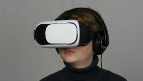 Tonåringpojken ser in i vita virtuell verklighetexponeringsglas eller VR och har gyckel på en vit bakgrund i studion Framtid är arkivfilmer