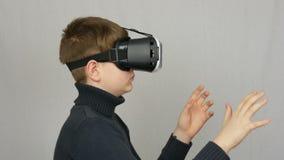 Tonåringpojken ser in i vita virtuell verklighetexponeringsglas eller VR och har gyckel på en vit bakgrund i studion Framtid är stock video