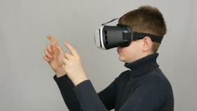 Tonåringpojken ser in i vita virtuell verklighetexponeringsglas eller VR och har gyckel på en vit bakgrund i studion Framtid är lager videofilmer