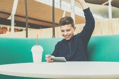 Tonåringpojken sitter på kafétabellen, spelar mobila lekar på smartphonen Pojken sitter med hans hand upp, segern, vinst arkivfoton