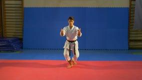 Tonåringpojken utför kata i sportkorridoren under hans karateutbildning lager videofilmer