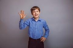Tonåringpojken vinkar hans hand på grå bakgrund Royaltyfri Fotografi