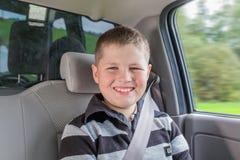 Tonåringsammanträde i en bil i säkerhetsstol Arkivfoton