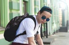 Tonåringsammanträde på momenten på stadsgatan fotografering för bildbyråer