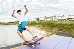 Tonåringskateboradåkaren i ett lock och kortslutningar på stänger på en skateboard i en skridsko parkerar arkivbild