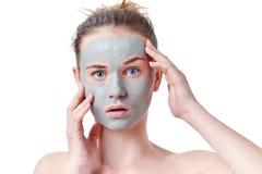 Tonåringskincarebegrepp Ung tonårig flicka med den torkade ansikts- maskeringen för lera som gör den roliga framsidan Royaltyfri Bild