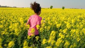Tonåringspring med en vattenflaska i fältet av gula blommor stock video
