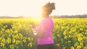 Tonåringspring och dricksvattenflaska i fält av gulingblommor på solnedgången arkivfilmer