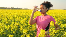 Tonåringspring och dricksvattenflaska i fältet av gula blommor arkivfilmer