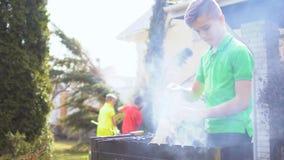 Tonåringuppsättningbrand för picknick i trädgården lager videofilmer