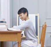 Tonårs- asiatisk pojke som hemma ler, lär & gör läxa Royaltyfri Bild