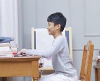 Tonårs- asiatisk pojke som surfar netto hemmastatt le Royaltyfri Fotografi