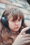 Tonårs- begrepp - tonårs- flicka med hörlurar som utanför lyssnar till musik Royaltyfria Foton
