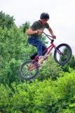 Tonårs- cyklist för BMX-fristil som högt hoppar Fotografering för Bildbyråer