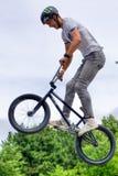 Tonårs- cyklist för BMX-fristil som hoppar över ramp Arkivbilder
