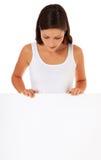 Tonårs- flicka bak blank vit signboard royaltyfri bild