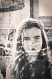 Tonårs- flicka bak en spindelrengöringsduk Arkivfoton
