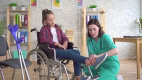 Tonårs- flicka efter en skada i en rullstol på mottagandet av en doktor stock video