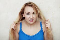 Tonårs- flicka för blond kvinna som visar henne skadat torrt hår Royaltyfri Foto