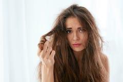 Tonårs- flicka för blond kvinna som visar henne skadat torrt hår Kvinna med torrt och skadat långt hår royaltyfri bild