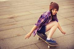 Tonårs- flicka för brunett i hipsterdräkt (jeans kortsluter, keds, plädskjorta, hatt), med en skateboard på parkera utomhus Arkivfoto