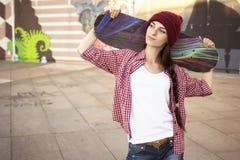 Tonårs- flicka för brunett i kortslutningar för hipsterdräktjeans, keds, plommoner Arkivfoto