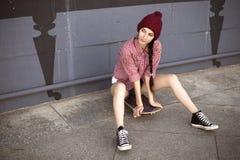 Tonårs- flicka för brunett i kortslutningar för hipsterdräktjeans, keds, plommoner Arkivfoton