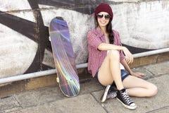 Tonårs- flicka för brunett i kortslutningar för hipsterdräktjeans, keds, plommoner Royaltyfria Foton