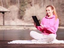 Tonårs- flicka för kvinna i träningsoverall genom att använda minnestavlan på den utomhus- pir Arkivfoto