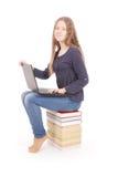 Tonårs- flicka för student som från sidan sitter på boken med bärbara datorn royaltyfri bild