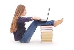 Tonårs- flicka för student som från sidan sitter på boken med bärbara datorn arkivbild