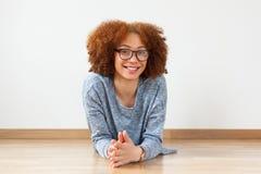 Tonårs- flicka för svart afrikansk amerikan som ner ligger på det wood golvet Arkivfoton