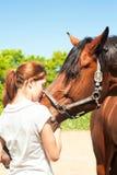 Tonårs- flicka för ung rödhårig man som kysser hennes favorit- kastanjebruna häst royaltyfri bild