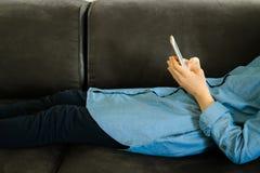 Tonårs- flicka i en blå klänning som lägger på en soffa, medan rymma en smart telefon med en tom skärm i händerna Anv?nda f?r ung arkivfoto