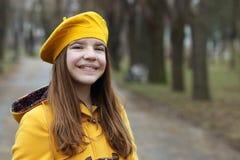 Tonårs- flicka i ett gul lag och basker royaltyfri foto