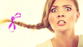 Tonårs- flicka i flätad trådhår som gör den ilskna framsidan Arkivfoton