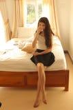 Tonårs- flicka i hemtrevligt lägenhetrum med stor vit säng arkivfoto
