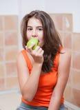 Tonårs- flicka i orange t-skjorta som äter ett grönt äpple Arkivbild