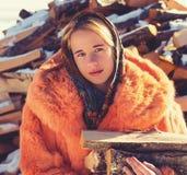 Tonårs- flicka i rött pälslag med något vedträ fotografering för bildbyråer