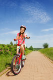 Tonårs- flicka i rött sammanträde på en cykel Fotografering för Bildbyråer