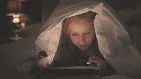 Tonårs- flicka i säng som spelar en minnestavla i social internet i det mörka ljuset Stäng sig upp av den hållande ögonen på vide lager videofilmer