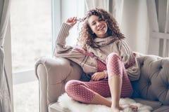 Tonårs- flicka i tröja och jumpsuit på en soffa royaltyfri foto