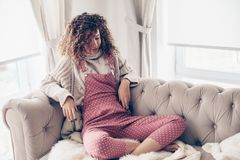 Tonårs- flicka i tröja och jumpsuit på en soffa royaltyfri bild